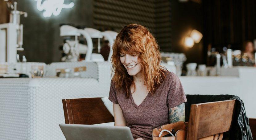 jeune femme souriante dans un café travaillant sur un ordinateur portable